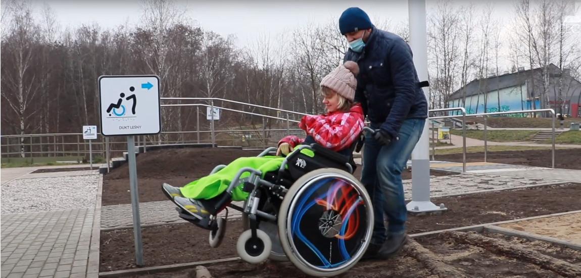 Osoba na wózku wraz z opiekunem pokonuje tor do nauki jazdy na wózku inwalidzkim