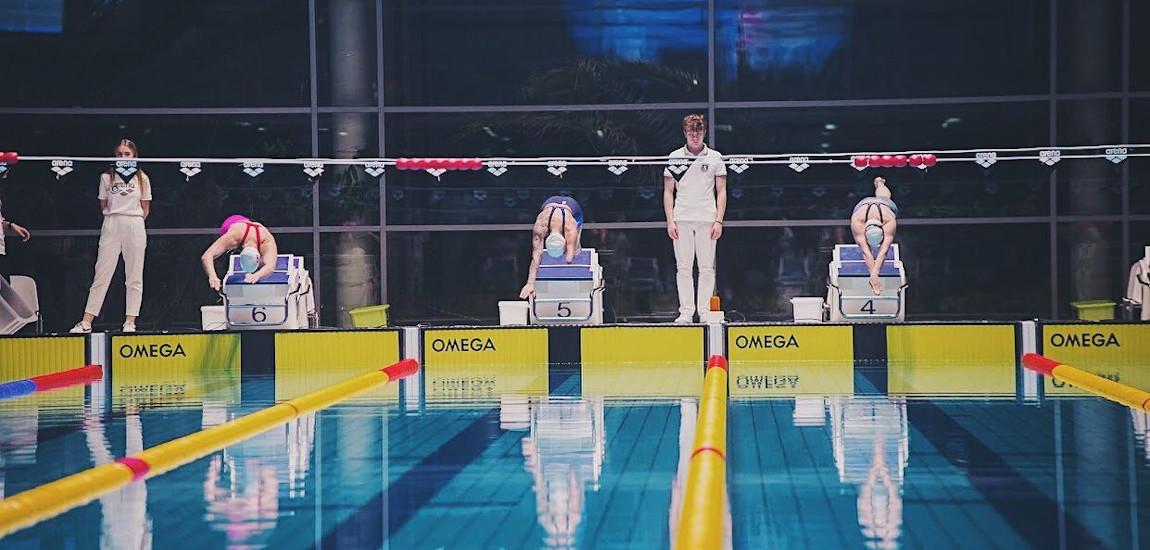 Zawodnicy startujący ze słupków startowych na basenie