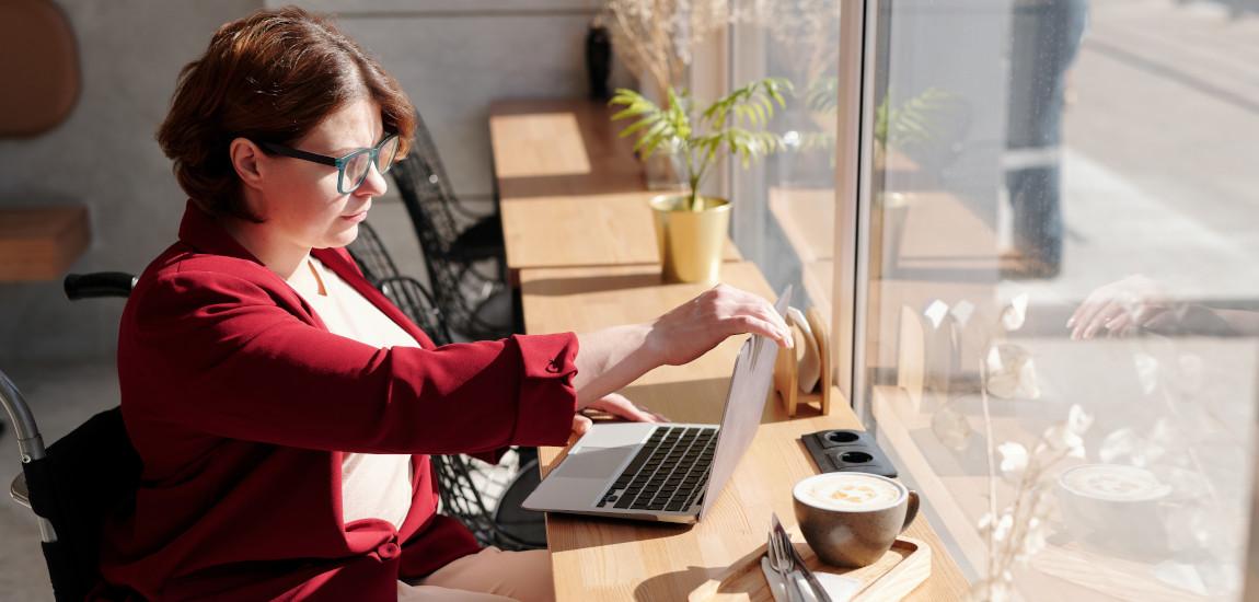Kobieta na wózku inwalidzkim pracująca przy laptopie