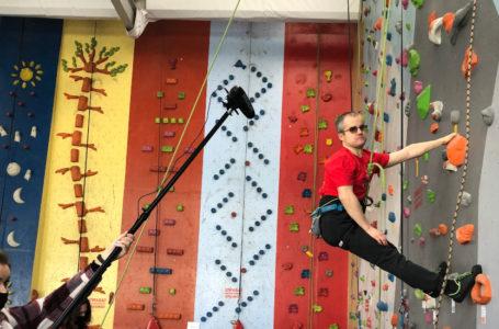 Andrzej Tikhonov wspinający się po ściance wspinaczkowej