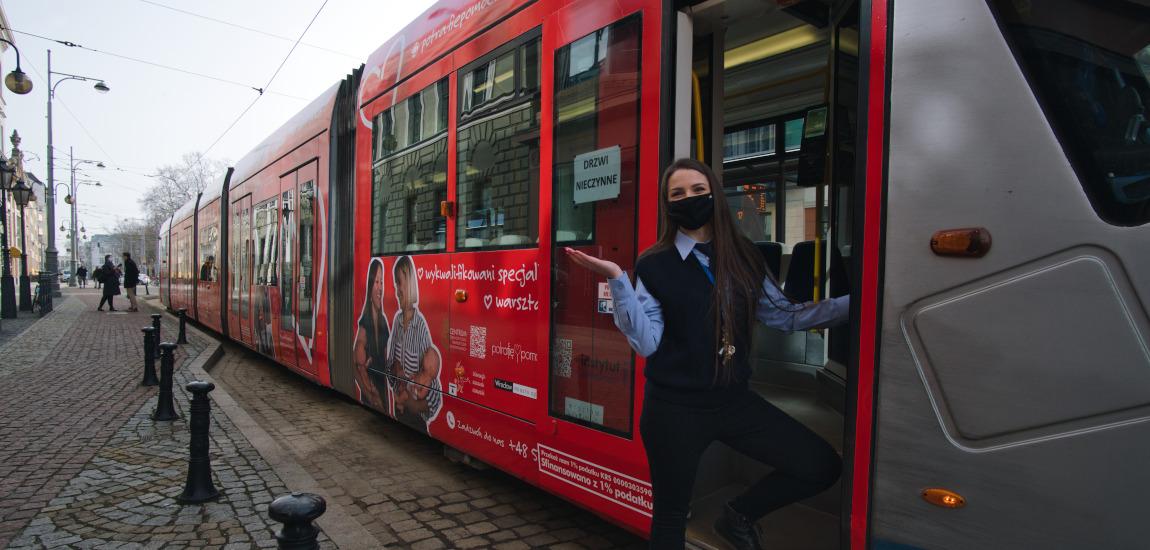 Kobieta wsiadająca do tramwaju w malowaniu kampanii