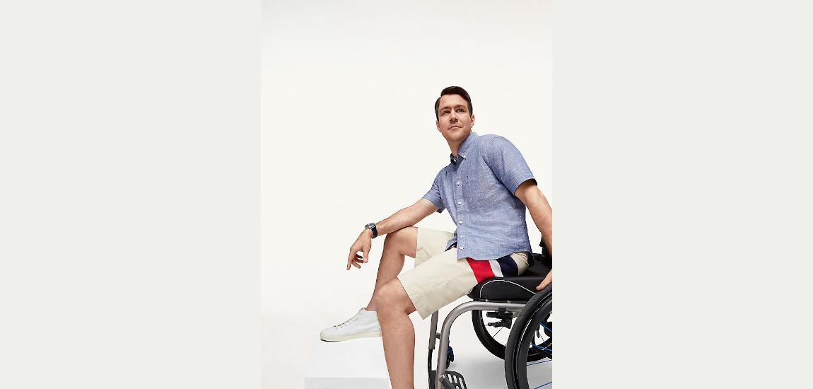 Mężczyzna ubrany w ubrania marki Tommy Hilfiger siedzący na wózku inwalidzkim