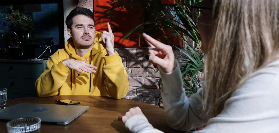 Dwie osoby migające przy stole