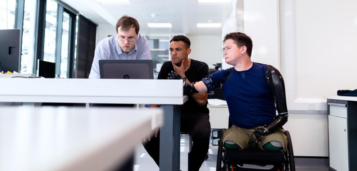 Mężczyzna na wózku z protezami rąk z kolegami z pracy przy komputerze
