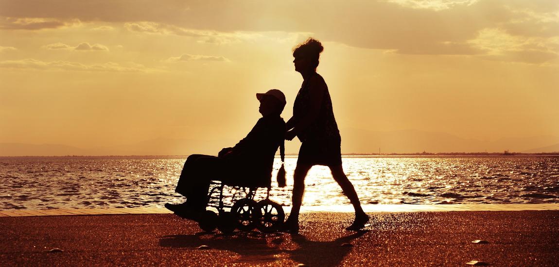Kobieta pchająca po plaży wózek ze starszym mężczyzną na tle zachodzącego słońca