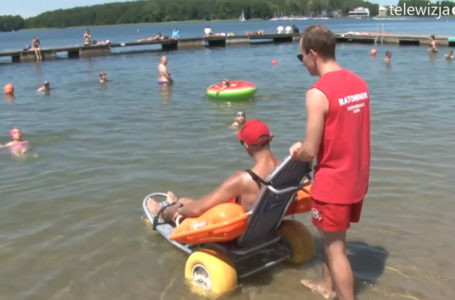 Osoba z niepełnosprawnością wjeżdżająca do wody na wózku-amfibii w asyście ratownika