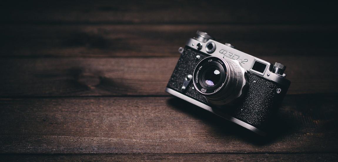 Analogowy, stary aparat fotograficzny leżący na drewnianym stole