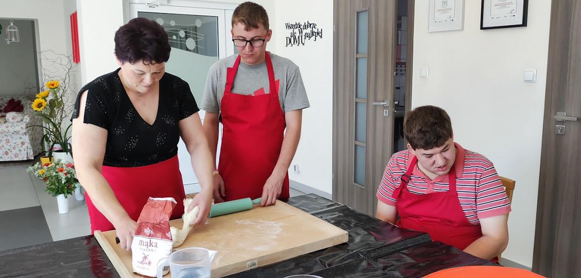 Dwie osoby z niepełnosprawnością pomagające asystentowi w kuchni