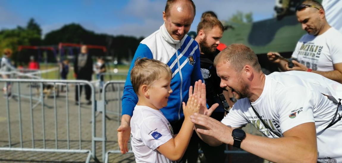 Wojciech Bobrowski przybijające piątkę niepełnosprawnemu dziecku