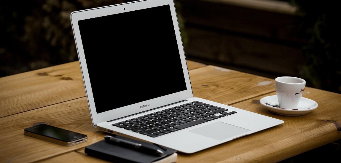 Laptop, telefon i filiżanka kawy na drewnianym stole