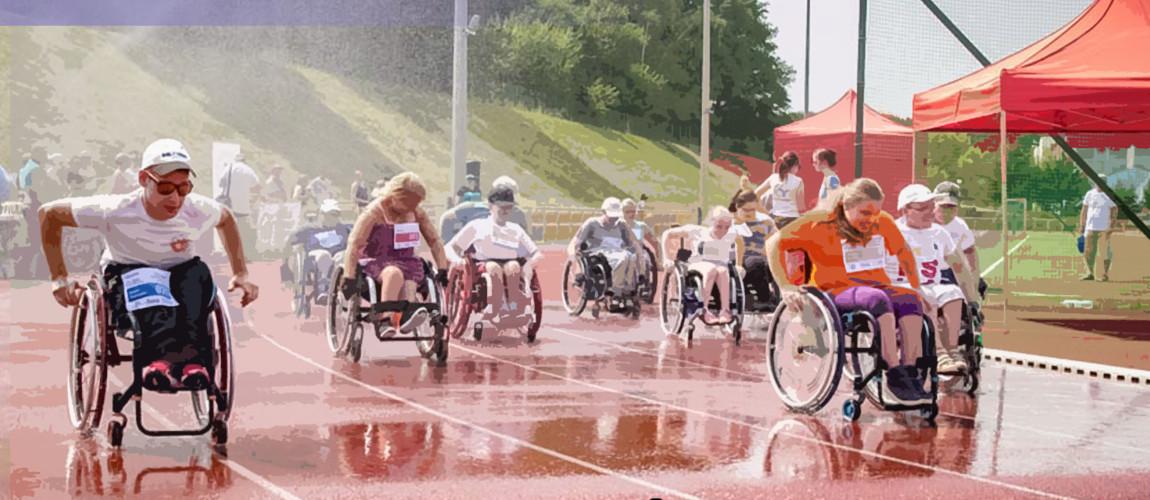 Zawodnicy jadący na wózkach po bieżni stadionu