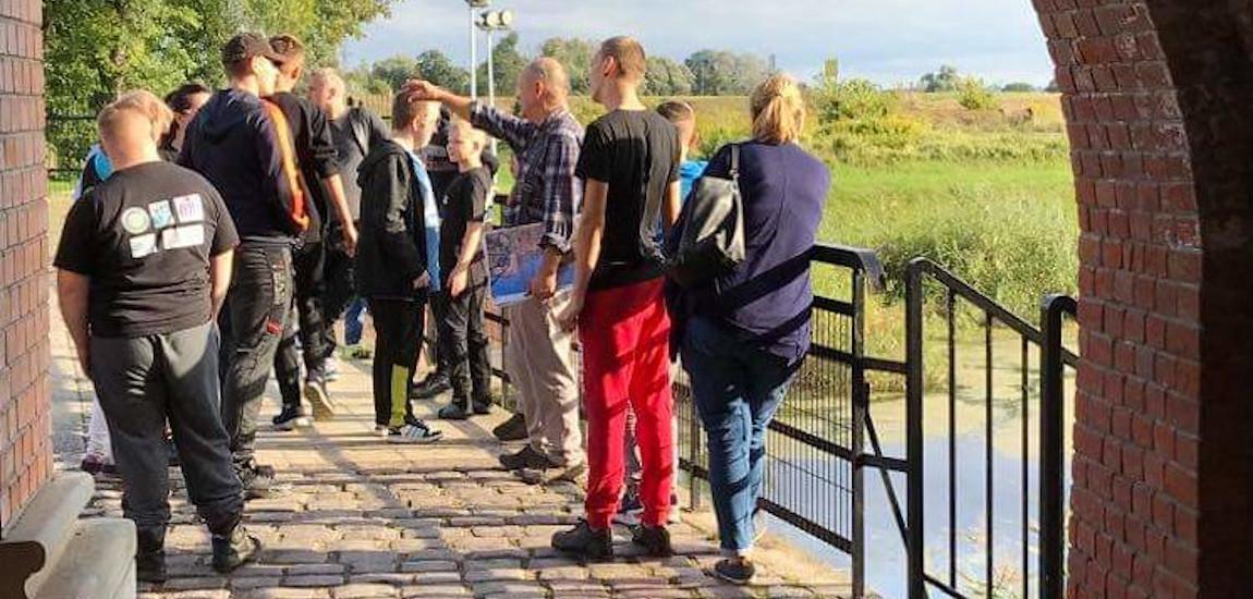 Grupa wychowanków obserwuje tereny przed jednym z obiektów Twierdzy Kostrzyn