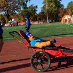 Przemysław Jurczak z synem na specjalistycznym wózku stoją na bieżni